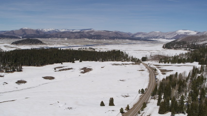 5.7K stock footage aerial video of flying by a deserted country road in snowy valley with view of mountains, New Mexico Aerial Stock Footage | DX0002_134_021