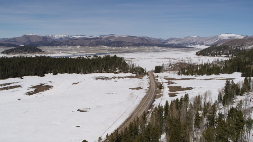 5.7K stock footage aerial video of a lonely country road in snowy valley with view of distant mountains, New Mexico Aerial Stock Footage | DX0002_134_023