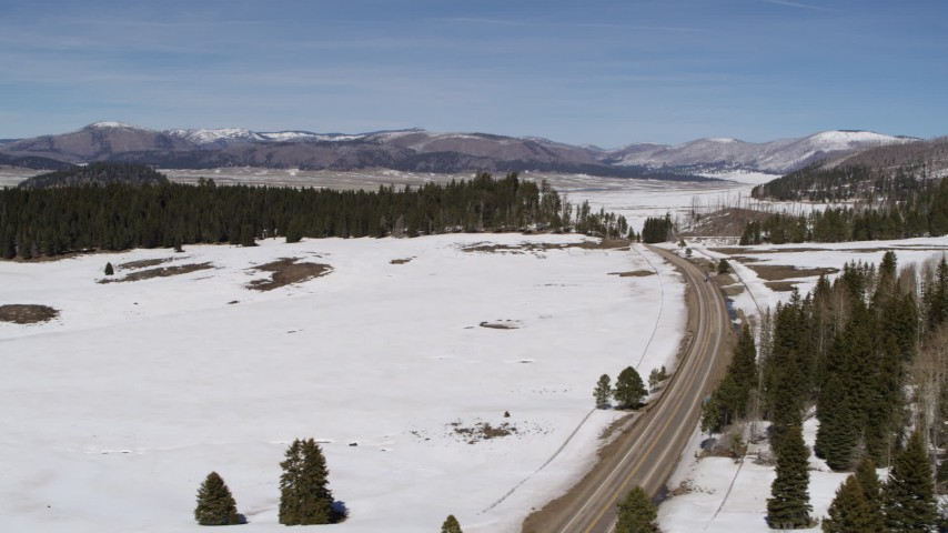 5.7K stock footage aerial video pass a lonely country road in snowy valley with view of distant mountains, New Mexico Aerial Stock Footage | DX0002_134_024