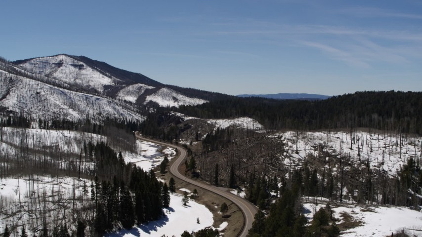 5.7K stock footage aerial video of following a winding road by snowy mountains, New Mexico Aerial Stock Footage | DX0002_134_029