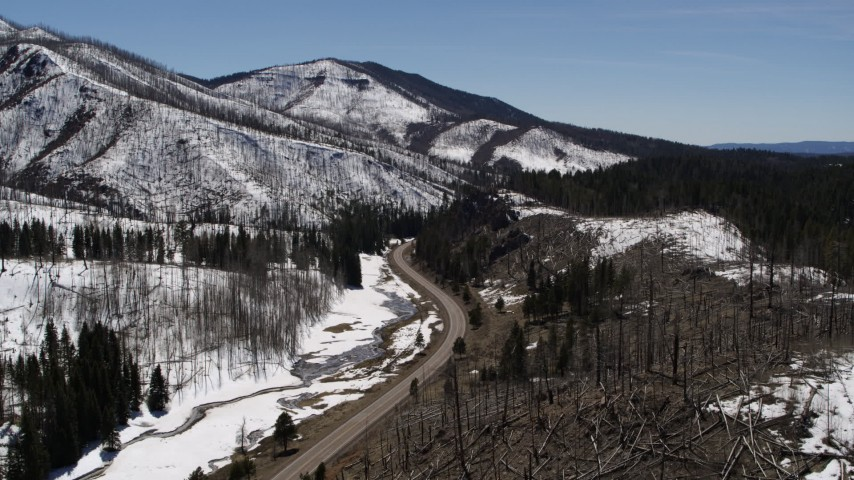 5.7K stock footage aerial video of following a winding road between snowy mountains and evergreens, New Mexico Aerial Stock Footage | DX0002_134_030