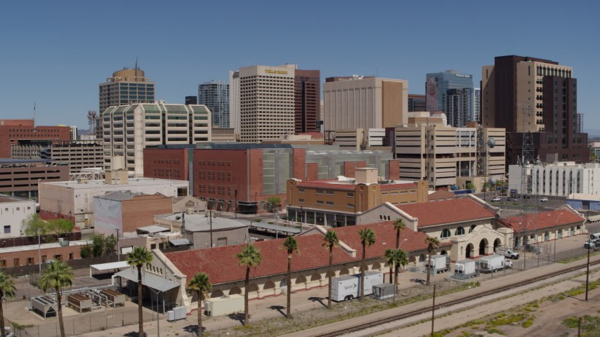 5.7K stock footage aerial video of flying away from a train station and the city's skyline, Downtown Phoenix, Arizona Aerial Stock Footage | DX0002_136_023