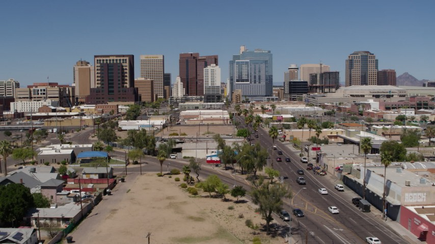 5.7K stock footage aerial video of a reverse view of tall office buildings seen from city streets, Downtown Phoenix, Arizona Aerial Stock Footage | DX0002_136_029