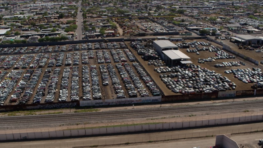 5.7K stock footage aerial video orbit and fly away from rows of cars at an automobile junkyard in Phoenix, Arizona Aerial Stock Footage | DX0002_137_009