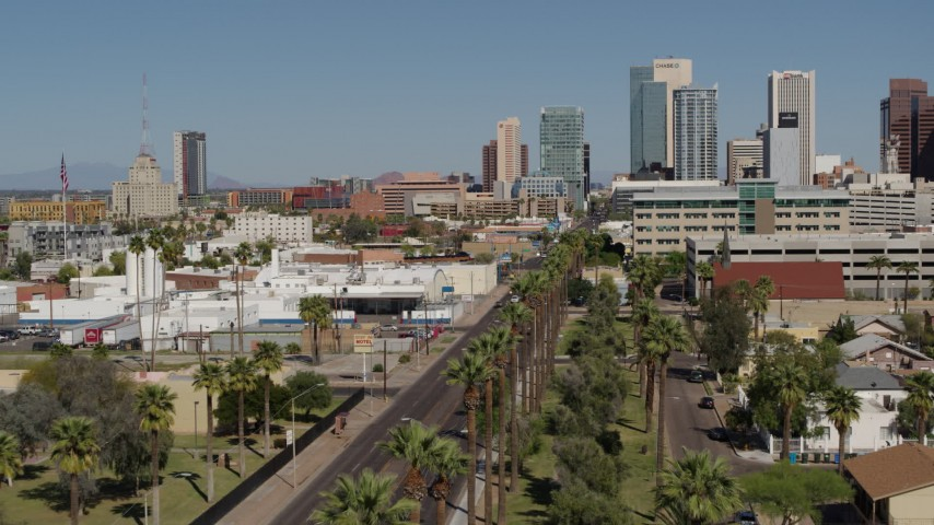5.7K stock footage aerial video fly over palm trees at city park toward tall office buildings in Downtown Phoenix, Arizona Aerial Stock Footage | DX0002_137_036