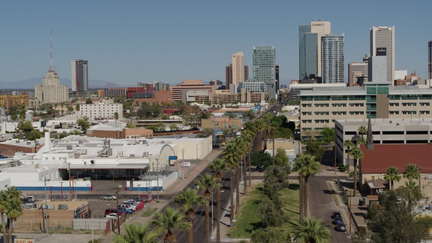 5.7K stock footage aerial video reverse view of palm trees at city park and tall office buildings in Downtown Phoenix, Arizona Aerial Stock Footage | DX0002_137_037