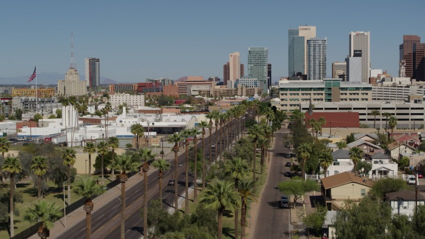 5.7K stock footage aerial video fly over city park palm trees toward tall office buildings in Downtown Phoenix, Arizona Aerial Stock Footage | DX0002_137_040