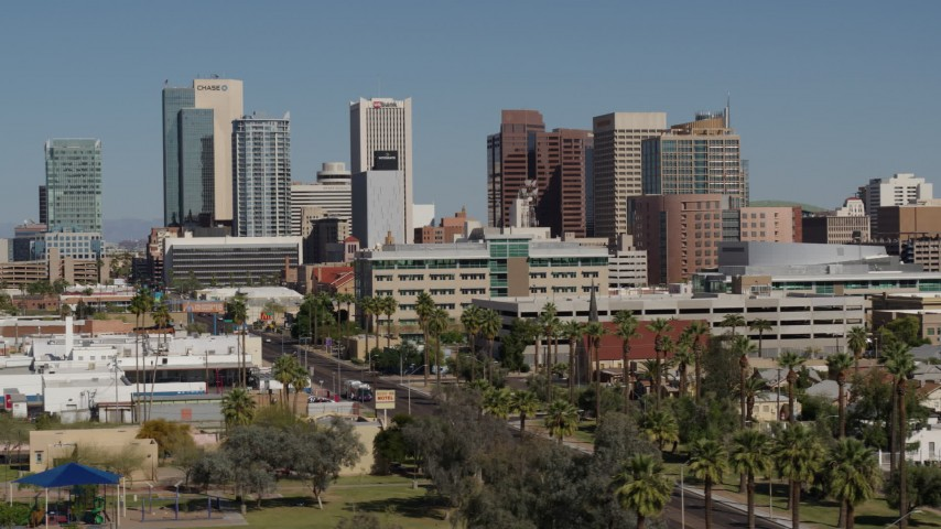 5.7K stock footage aerial video of towering office buildings seen from street lined with palm trees in Downtown Phoenix, Arizona Aerial Stock Footage DX0002_137_053 | Axiom Images