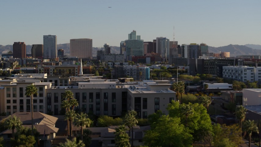 5.7K stock footage aerial video of a view over rooftops at high-rise office buildings in the distance in Downtown Phoenix, Arizona Aerial Stock Footage | DX0002_138_033