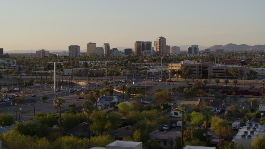 5.7K stock footage aerial video of tall office buildings in the distance at sunset in Phoenix, Arizona Aerial Stock Footage | DX0002_138_052