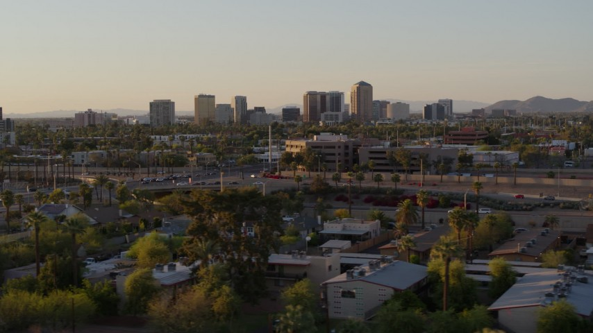 5.7K stock footage aerial video of towering office buildings in the distance at sunset in Phoenix, Arizona Aerial Stock Footage | DX0002_138_053