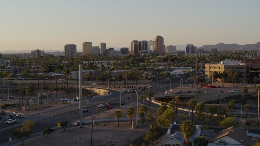 5.7K stock footage aerial video of towering office buildings in the distance at sunset in Phoenix, Arizona Aerial Stock Footage | DX0002_138_054