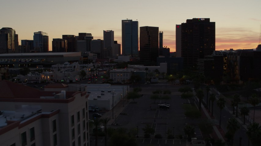 5.7K stock footage aerial video of passing college buildings to focus on office high-rises at sunset in Downtown Phoenix, Arizona Aerial Stock Footage   DX0002_139_006