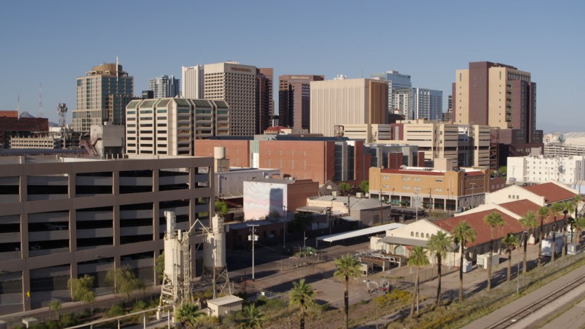 5.7K stock footage aerial video of the city's skyline seen between a parking garage and train station in Downtown Phoenix, Arizona Aerial Stock Footage | DX0002_142_019