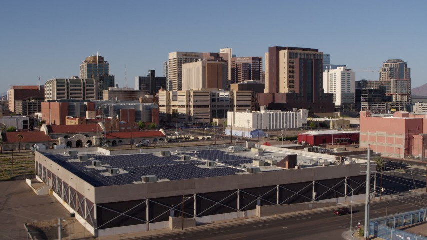 5.7K stock footage aerial video of the city's skyline seen while flying past train station in Downtown Phoenix, Arizona Aerial Stock Footage   DX0002_142_023