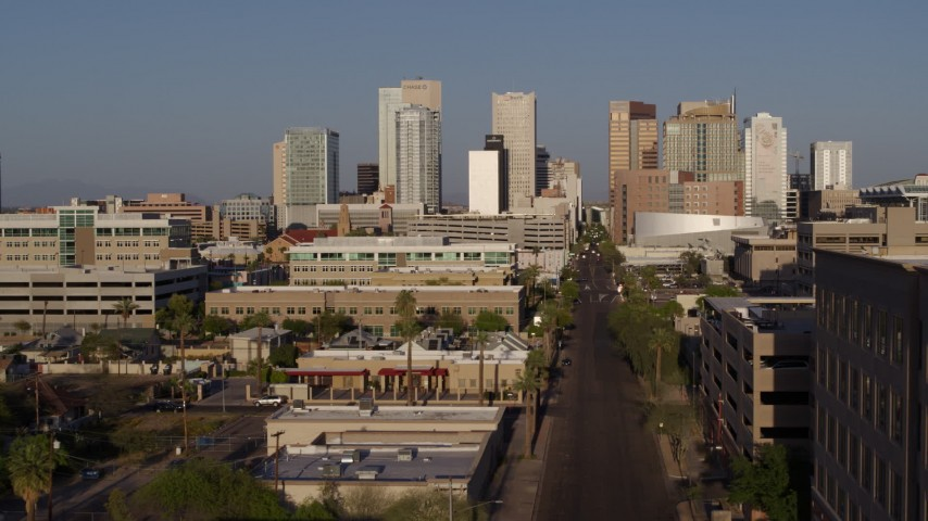 5.7K stock footage aerial video flyby and away from high-rise office buildings of the city's skyline and Adams Street at sunset in Downtown Phoenix, Arizona Aerial Stock Footage   DX0002_143_002