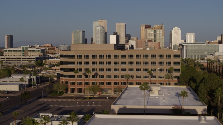 5.7K stock footage aerial video flying by state offices to reveal Adams Street leading to the city's skyline at sunset in Downtown Phoenix, Arizona Aerial Stock Footage | DX0002_143_006