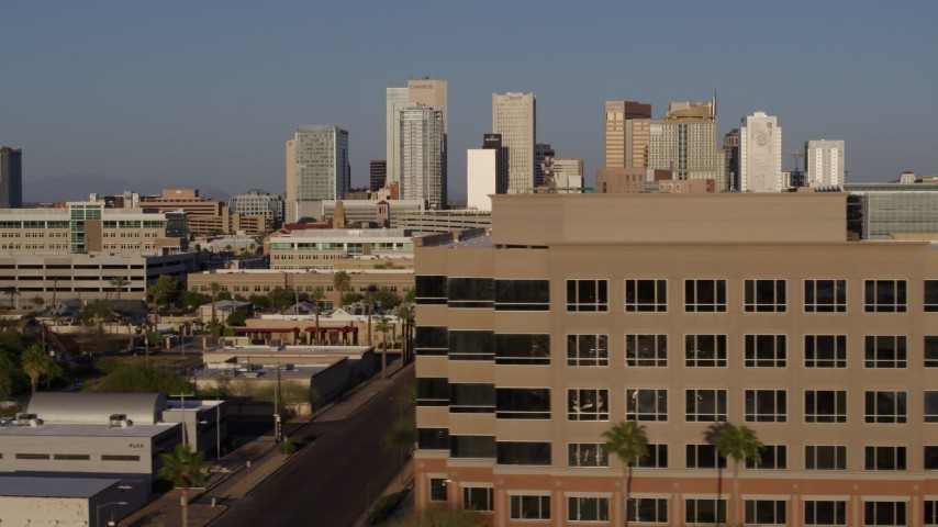 5.7K stock footage aerial video flying by state offices to reveal Adams Street leading to the city's skyline at sunset in Downtown Phoenix, Arizona Aerial Stock Footage | DX0002_143_008