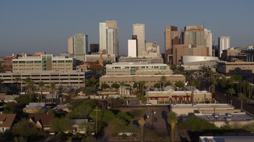 5.7K stock footage aerial video reverse view of city's skyline at sunset, cross street to reveal state building in Downtown Phoenix, Arizona Aerial Stock Footage | DX0002_143_010