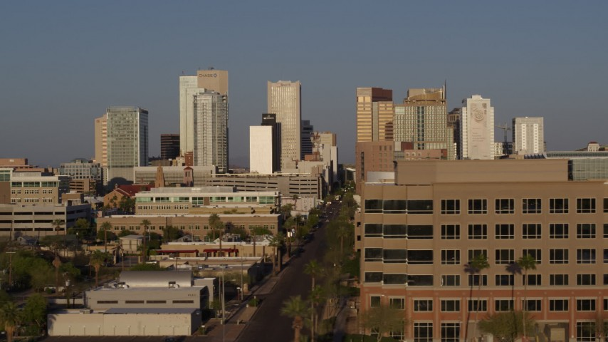 5.7K stock footage aerial video flyby Adams Street and state office building, focus on city's skyline at sunset, Downtown Phoenix, Arizona Aerial Stock Footage | DX0002_143_014