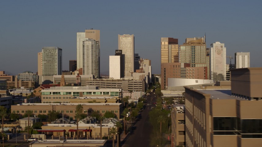 5.7K stock footage aerial video focus on city's skyline at sunset, flyby rooftop to reveal Adams Street, Downtown Phoenix, Arizona Aerial Stock Footage | DX0002_143_017