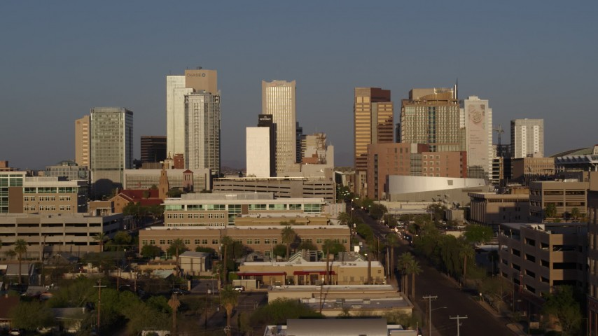 5.7K stock footage aerial video reverse view of city's skyline and Adams Street at sunset, Downtown Phoenix, Arizona Aerial Stock Footage | DX0002_143_023