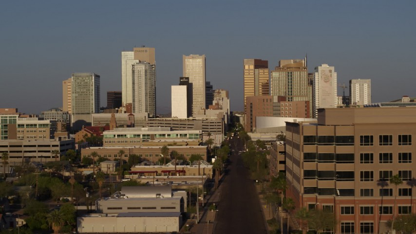 5.7K stock footage aerial video the city's skyline at sunset while passing Adams Street, Downtown Phoenix, Arizona Aerial Stock Footage | DX0002_143_024