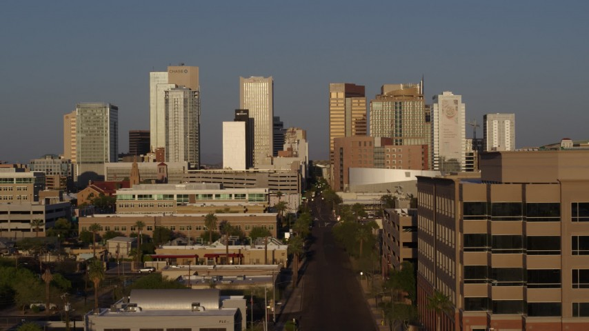 5.7K stock footage aerial video follow Adams Street toward skyline of Downtown Phoenix, Arizona, sunset Aerial Stock Footage | DX0002_143_025