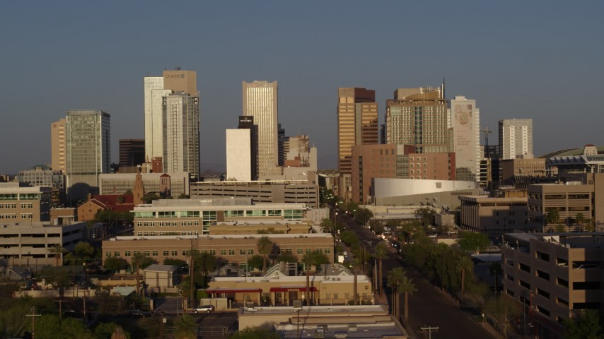 5.7K stock footage aerial video reverse view of skyline at sunset, descend near Adams Street Downtown Phoenix, Arizona Aerial Stock Footage | DX0002_143_026