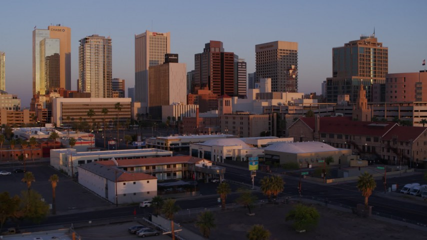 5.7K stock footage aerial video of passing by tall office towers in the city's skyline at sunset before descent, Downtown Phoenix, Arizona Aerial Stock Footage   DX0002_143_043