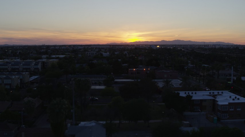 5.7K stock footage aerial video of the sun setting behind distant mountains, seen from Phoenix, Arizona Aerial Stock Footage | DX0002_143_051