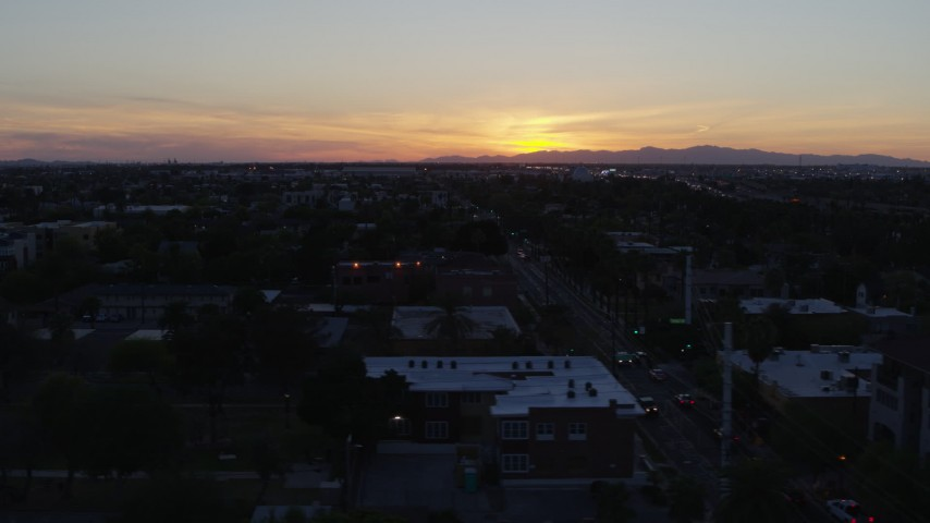 5.7K stock footage aerial video of a view of the sun setting behind distant mountains, seen from Phoenix, Arizona Aerial Stock Footage | DX0002_143_052