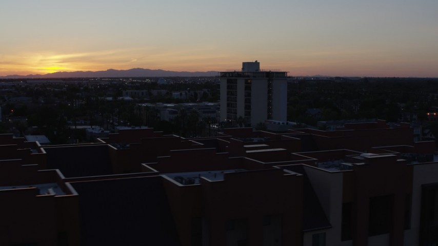 5.7K stock footage aerial video orbit apartment complex with the sun setting behind distant mountains, seen from Phoenix, Arizona Aerial Stock Footage | DX0002_143_053