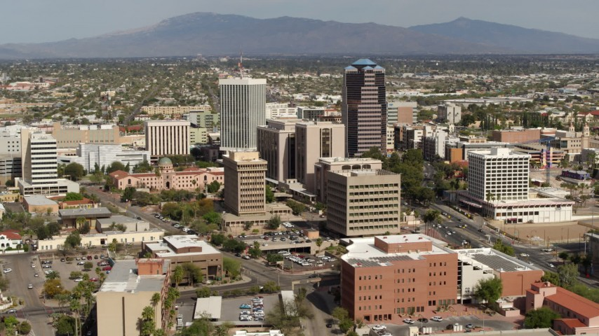 5.7K stock footage aerial video passing tall office high-rises surrounded by city buildings, then descend in Downtown Tucson, Arizona Aerial Stock Footage | DX0002_144_037