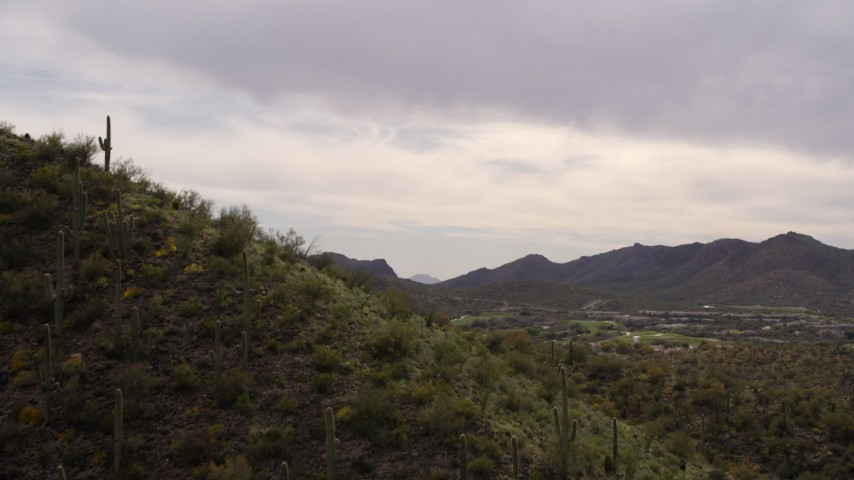 5.7K stock footage aerial video fly over small peak with cactus plants, reveals homes and golf course in Tucson, Arizona Aerial Stock Footage DX0002_145_002