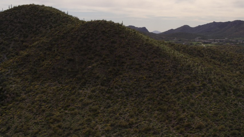 5.7K stock footage aerial video fly away from a small peak with cactus plants in Tucson, Arizona Aerial Stock Footage | DX0002_145_004