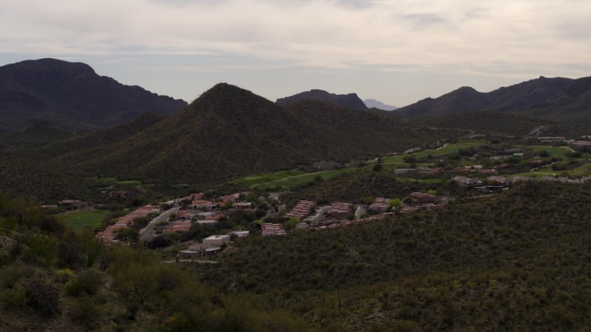 5.7K stock footage aerial video reverse view of homes and golf course, reveal small peak with cactus plants in Tucson, Arizona Aerial Stock Footage DX0002_145_007 | Axiom Images