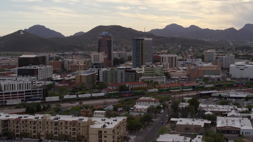 5.7K stock footage aerial video orbit office towers as a train passes, with Sentinel Peak in the background, Downtown Tucson, Arizona Aerial Stock Footage DX0002_145_036 | Axiom Images