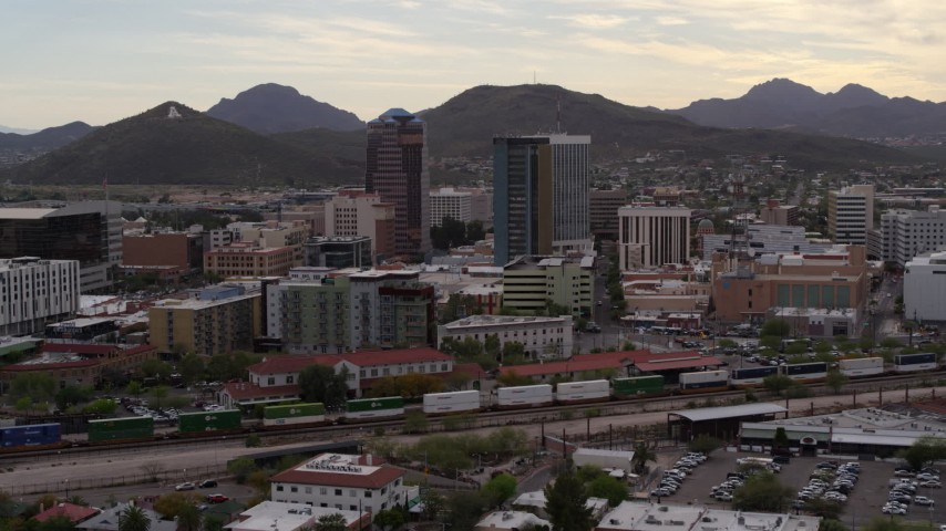 5.7K stock footage aerial video approach office towers as a train passes, with Sentinel Peak in the background, Downtown Tucson, Arizona Aerial Stock Footage | DX0002_145_037