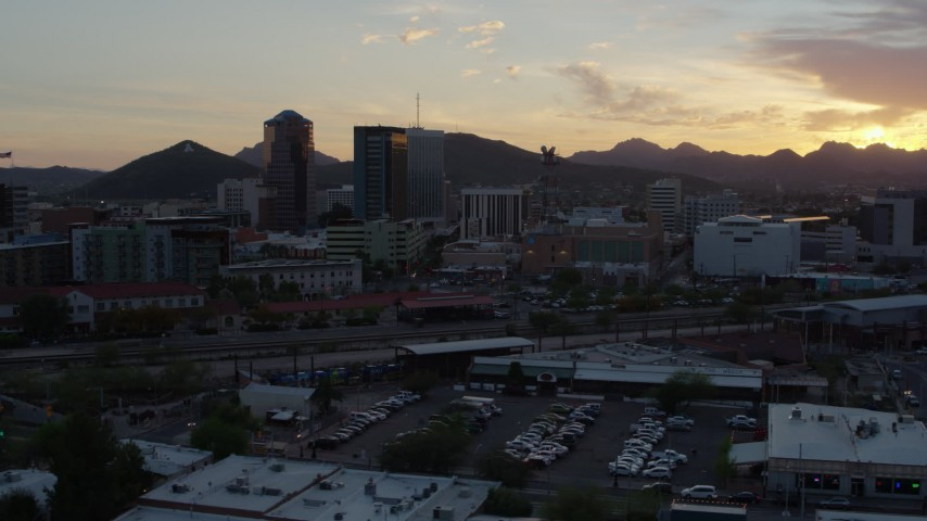 5.7K stock footage aerial video fly low by railroad tracks with view of high-rise office towers, and setting sun in Downtown Tucson, Arizona Aerial Stock Footage | DX0002_146_036