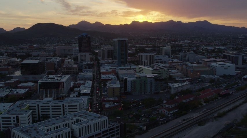 5.7K stock footage aerial video fly away from and past high-rise office towers with view of Sentinel Peak at sunset in Downtown Tucson, Arizona Aerial Stock Footage DX0002_146_041