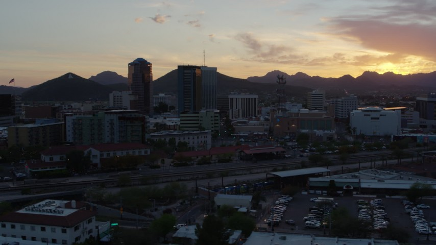 5.7K stock footage aerial video flyby railroad tracks while focused on high-rise office towers at sunset in Downtown Tucson, Arizona Aerial Stock Footage DX0002_146_043 | Axiom Images