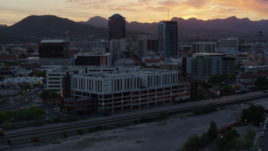5.7K stock footage aerial video focusing on high-rise office towers at sunset while flying away from Downtown Tucson, Arizona Aerial Stock Footage | DX0002_147_003