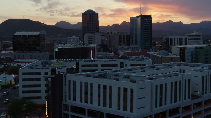 5.7K stock footage aerial video of a view of high-rise office towers at sunset with mountains in distance, Downtown Tucson, Arizona Aerial Stock Footage | DX0002_147_008