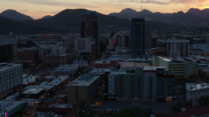 5.7K stock footage aerial video reverse view of office towers at sunset with mountains in distance, Downtown Tucson, Arizona Aerial Stock Footage | DX0002_147_010