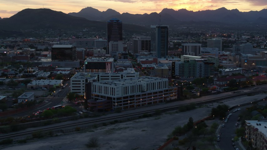 5.7K stock footage aerial video flyby office towers at sunset with mountains in distance, Downtown Tucson, Arizona Aerial Stock Footage | DX0002_147_011