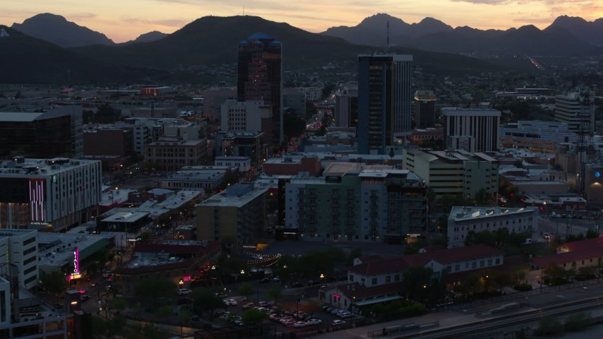 5.7K stock footage aerial video passing office towers at sunset with mountains in distance, Downtown Tucson, Arizona Aerial Stock Footage | DX0002_147_012