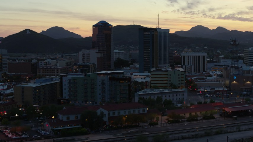 5.7K stock footage aerial video pass by office towers at sunset with mountains in background, Downtown Tucson, Arizona Aerial Stock Footage | DX0002_147_013