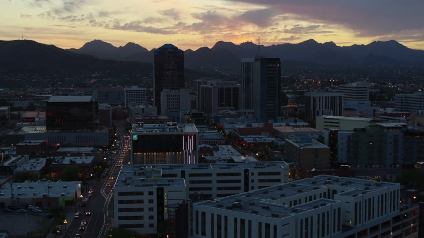 5.7K stock footage aerial video a reverse view of office towers at sunset with mountains in background, Downtown Tucson, Arizona Aerial Stock Footage | DX0002_147_014
