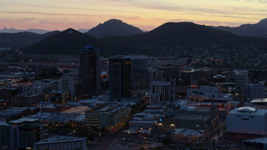 5.7K stock footage aerial video of passing tall office towers at sunset, Sentinel Peak in the distance, Downtown Tucson, Arizona Aerial Stock Footage DX0002_147_019 | Axiom Images